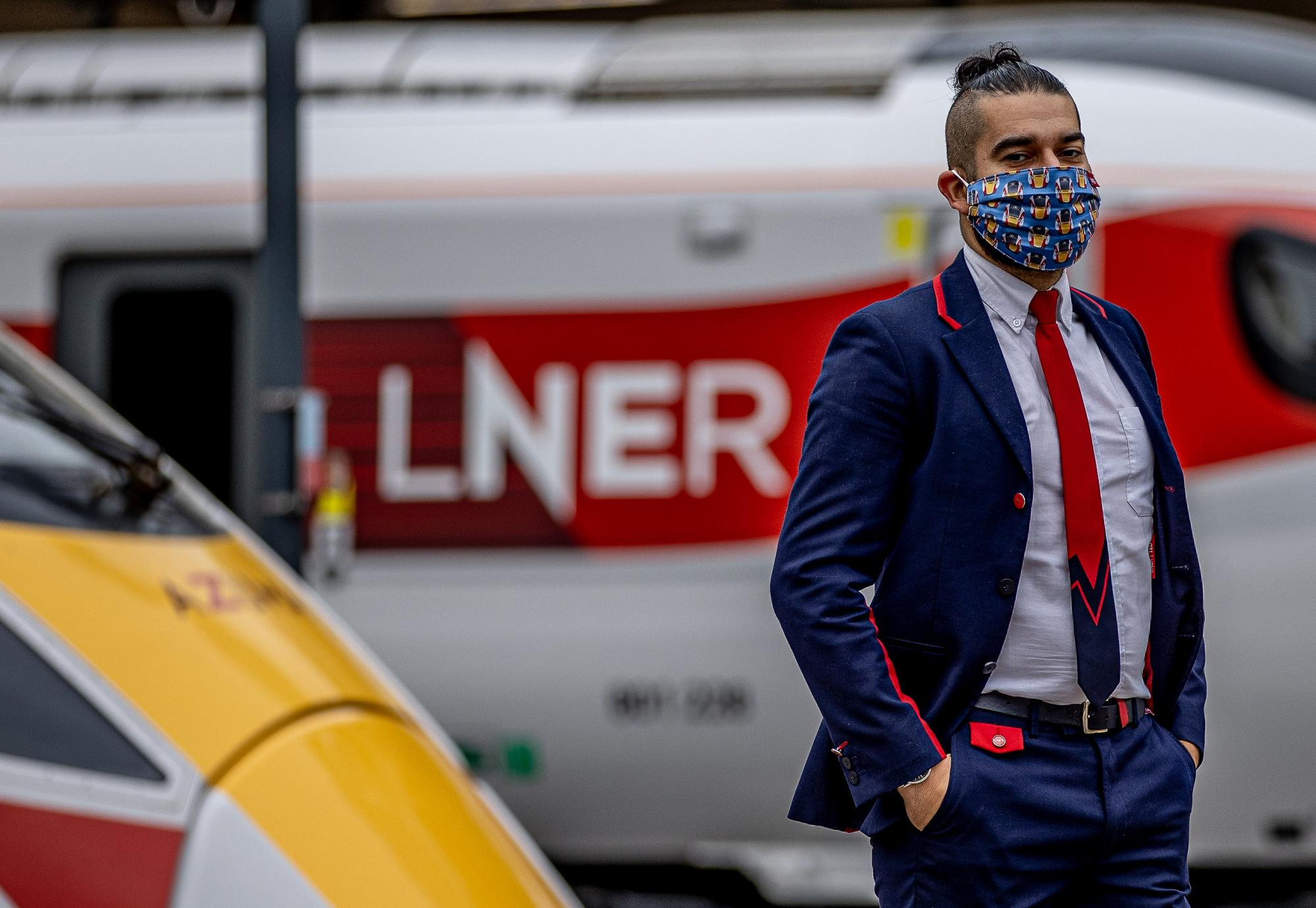 LNER Station Support Assistant Emrah Mehmet wearing the LNER Azuma Mask at London King's Cross Station.