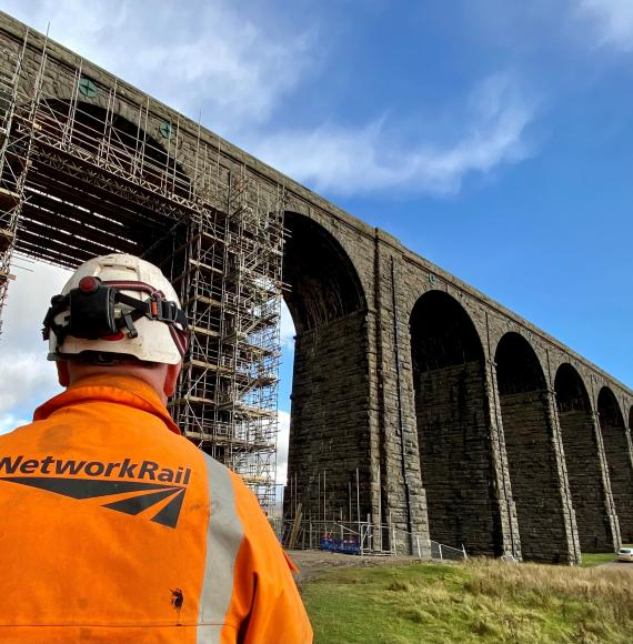 Ribblehead viaduct with a Network Rail worker in the foreground