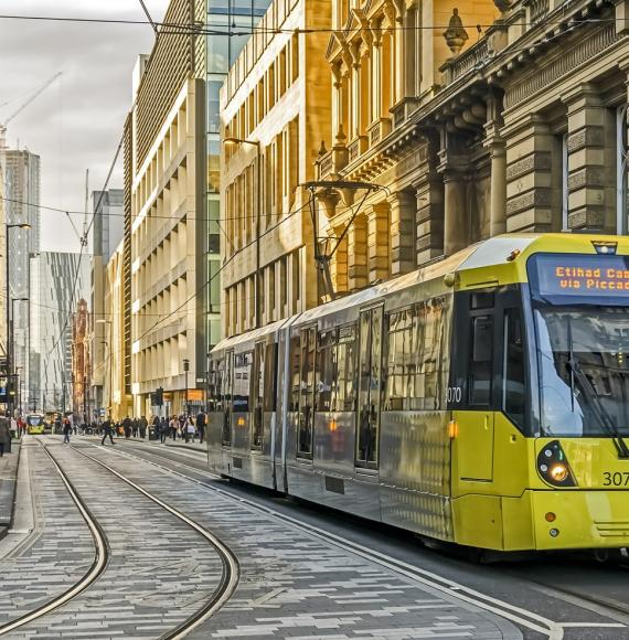 View of Manchester city centre, UK. A tram can be seen approaching and people can be seen walking on the roads.
