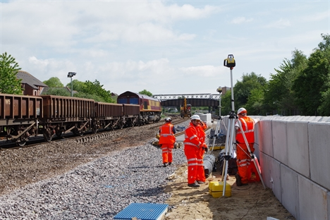 6WO3 waits to depart Longdyke with spent ballast whilst operatives wait by the wall