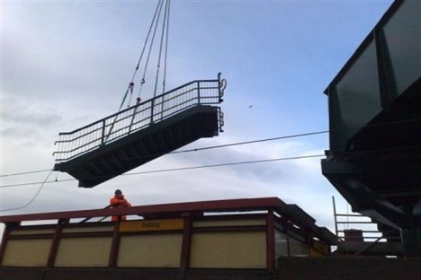 New bridge lifted into place over rail lines