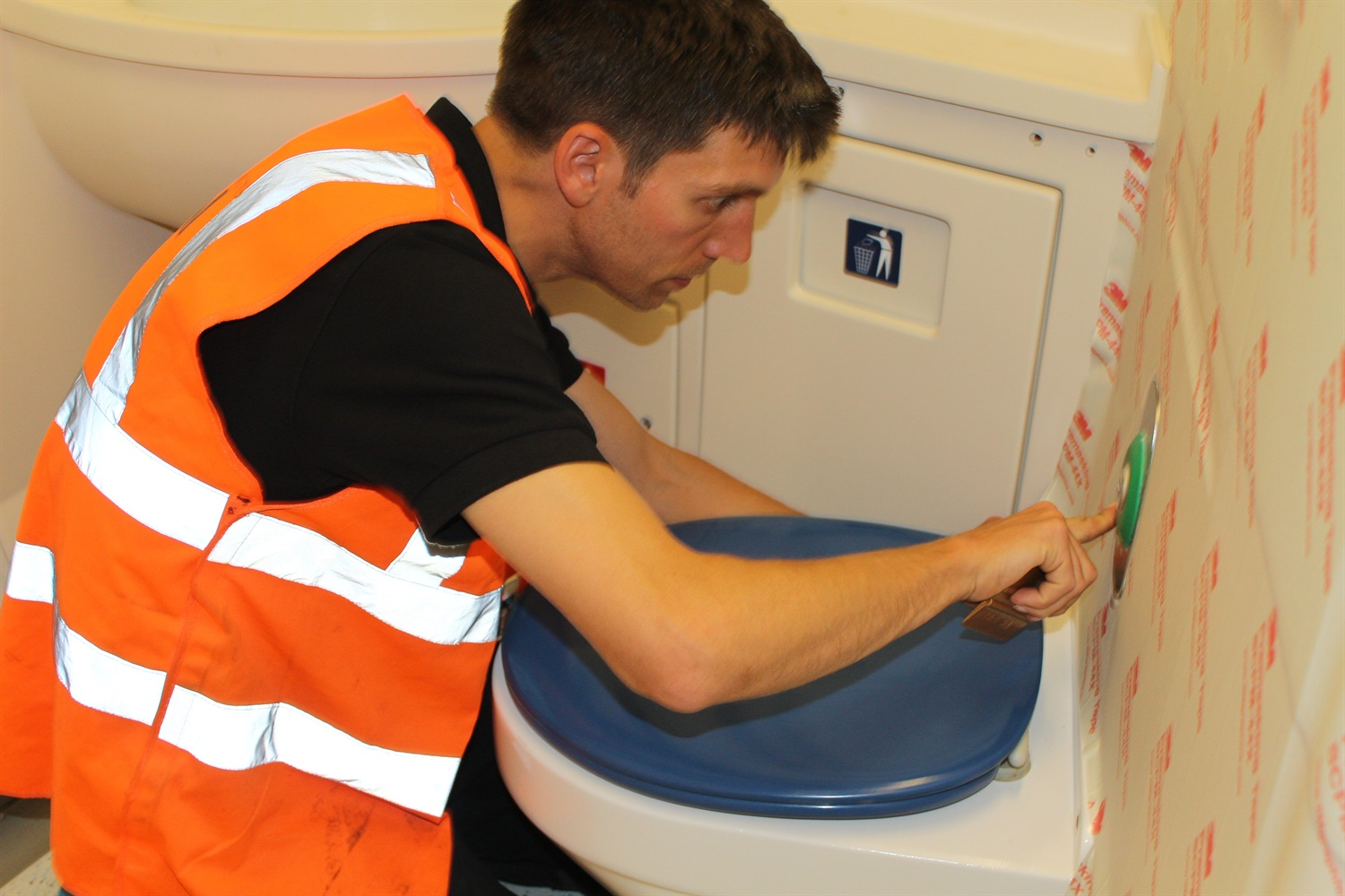 Worker refurbishing and putting screen prints on Class 375 train toilet